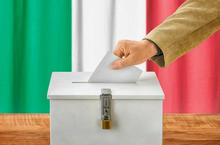 encuestando: Hombre poniendo una papeleta en una urna - Italia