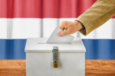 balloting: Man putting a ballot into a voting box - Netherlands