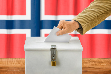 nomination: Man putting a ballot into a voting box - Norway Stock Photo