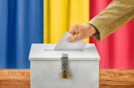 plebiscite: Man putting a ballot into a voting box - Romania