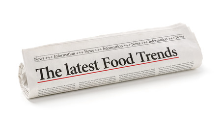 articles: Rolled newspaper with the headline The latest Food Trends Stock Photo