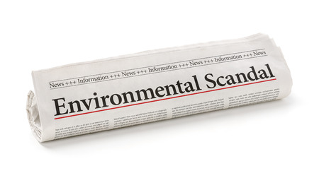 scandal: Rolled newspaper with the headline Environmental Scandal Stock Photo