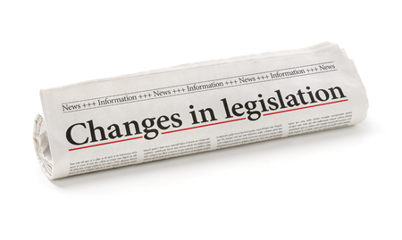 Rolled newspaper with the headline Changes in legislation 스톡 콘텐츠
