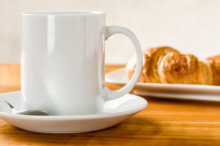mugs of coffee: A coffee mug with croissants