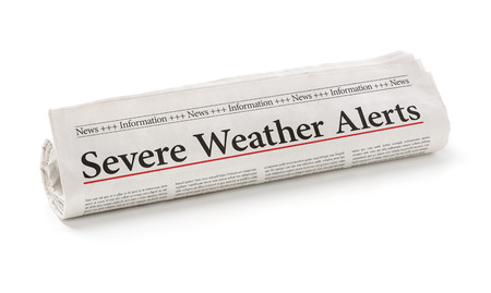 severe weather: Rolled newspaper with the headline Severe Weather Alerts