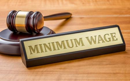 salarios: Un martillo y una placa de identificación con el salario mínimo de grabado