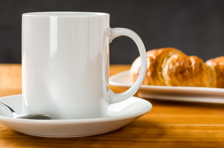 coffee spoon: A coffee mug with croissants on a dark background