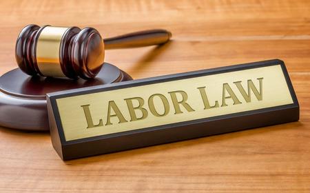 ley: Un martillo y una placa de identificación con la Ley del Trabajo de grabado Foto de archivo