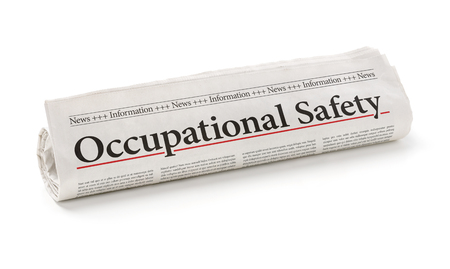 headline: Rolled newspaper with the headline Occupational Safety