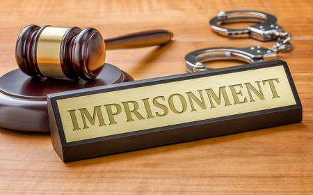 derecho penal: Un martillo y una placa de identificación con el encarcelamiento de grabado