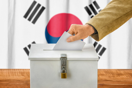 state election: Man putting a ballot into a voting box - South Korea Stock Photo