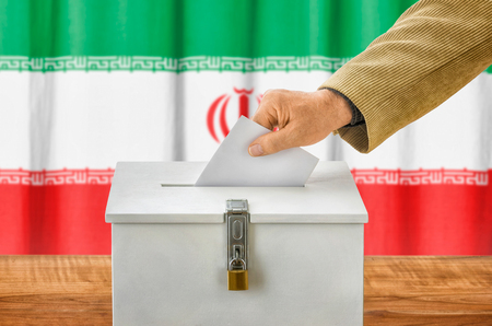 state election: Man putting a ballot into a voting box - Iran