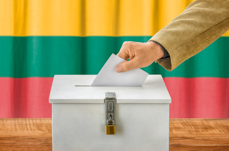 people voting: Man putting a ballot into a voting box - Lithuania