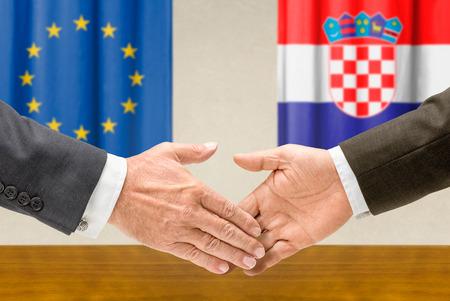 representatives: Representatives of the EU and Croatia shake hands