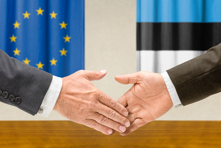 representatives: Representatives of the EU and Estonia shake hands Stock Photo