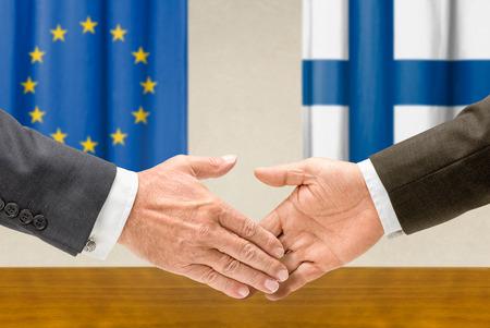 representatives: Representatives of the EU and Finland shake hands