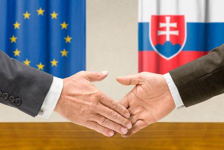 representatives: Representatives of the EU and Slovakia shake hands Stock Photo