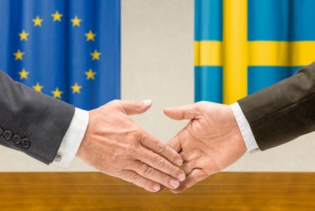 representatives: Representatives of the EU and Sweden shake hands