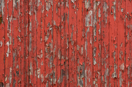 Weathered wooden boards with peeling red paint