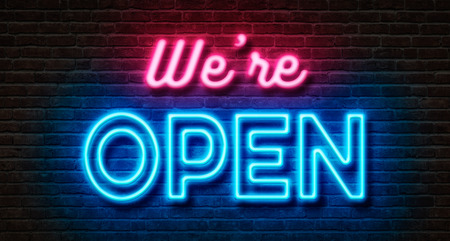 Neon sign on a brick wall - We are open Stockfoto