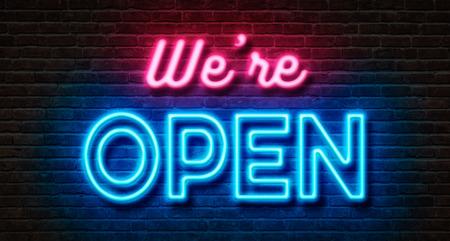 Neon sign on a brick wall - We are open Archivio Fotografico