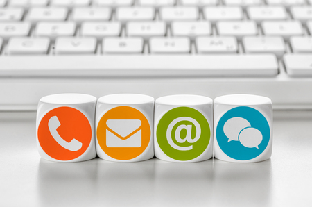 kommunikation: Brev tärning framför ett tangentbord - Kontakta Stockfoto
