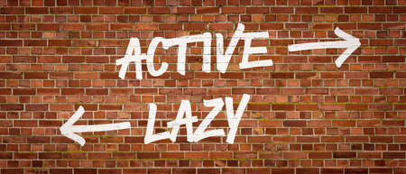 lethargy: Active or Lazy written on a brick wall Stock Photo