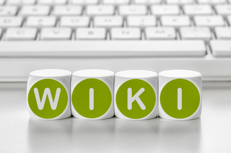 wiki: Letter dice in front of a keyboard - Wiki Stock Photo