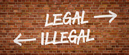 immigrants: Legal or Illegal written on a brick wall