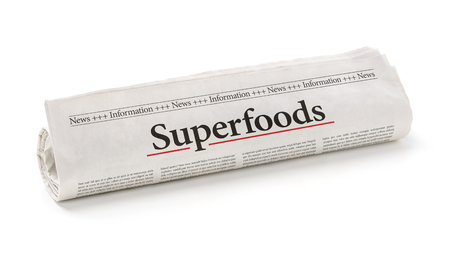 Rolled newspaper with the headline Superfoods