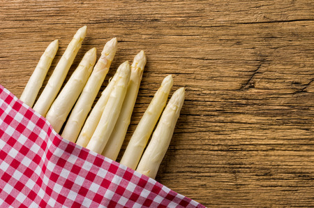 menue: White asparagus on a wooden board with a checkered tablecloth