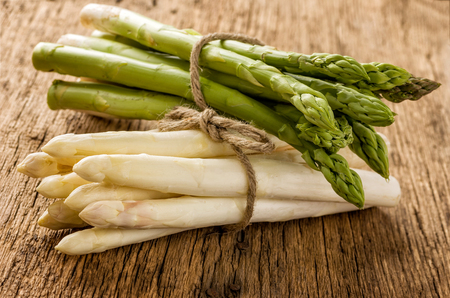 menue: Fresh green and white asparagus on a wooden background