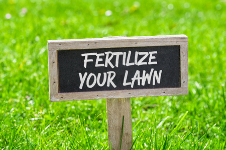 Sign on a green lawn - Fertilize your lawn