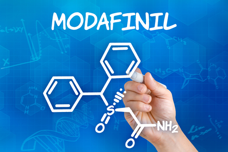 apnea: Hand with pen drawing the chemical formula of Modafinil Stock Photo