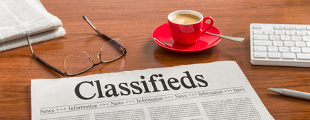 classifieds: A newspaper on a wooden desk - Classifieds Stock Photo