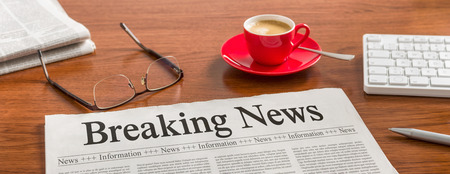 business report: A newspaper on a wooden desk - Breaking News
