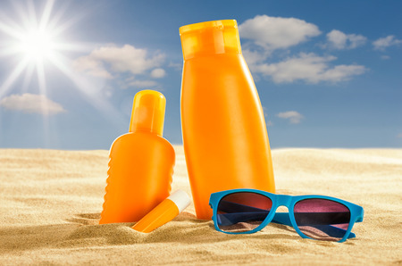 Various sunsreen products in the sand