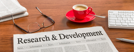 Noviny na dřevěném stole - Výzkum a vývoj Reklamní fotografie