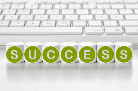 Letter dice in front of a keyboard - Success Stock Photo