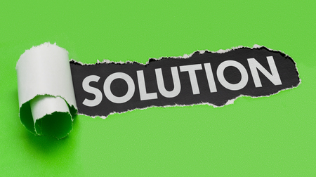 Torn green paper revealing the word Solution Stock Photo