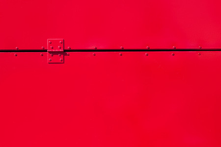 hinge: Red painted metal background with rivets and a hinge Stock Photo