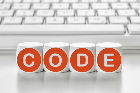 Letter dice in front of a keyboard - Code Stock Photo