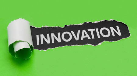 Torn green paper revealing the word Innovation