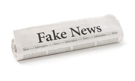 偽のニュースの見出しに丸めた新聞紙