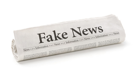 Rolled newspaper with the headline Fake News Stockfoto