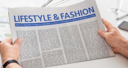 the latest models: Man reading newspaper with the headline Lifestyle and Fashion