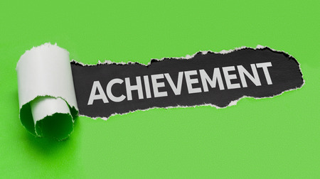 Torn green paper revealing the word Achievement