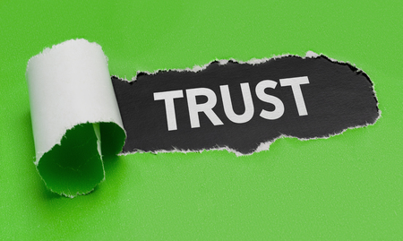 Torn green paper revealing the word Trust Stock Photo