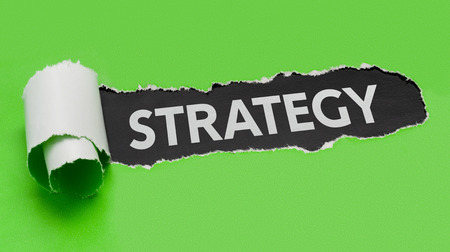 revealing: Torn green paper revealing the word Strategy