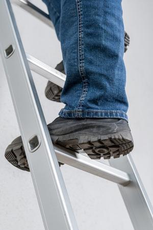 Ein Mann steht auf einer Leiter Standard-Bild - 75174860